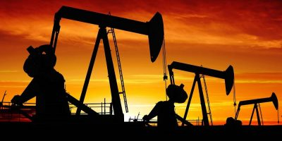 oil pumpjacks in silhouette at sunset, panoramic frame